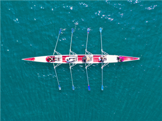 Aerial drone top panoramic view of sport canoe rowing synchronous athletes competing