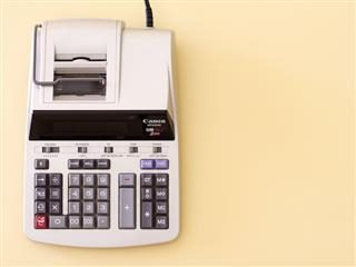 accountant's calculator sitting on a beige background