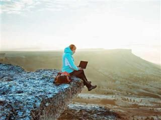 A woman sitting on the edge of a cliff with her laptop