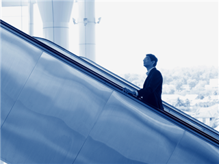 A businessman going up escalator with a giant window in the background overlooking the suburbs - improvement concept