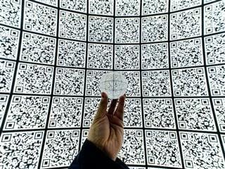 a wall  of QR codes as seen through a crystal ball