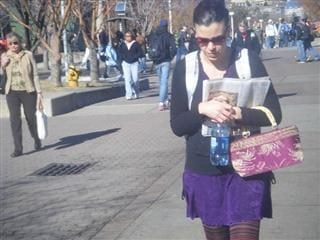 Woman holds a newspaper, a bag and a cup as she walks outside.