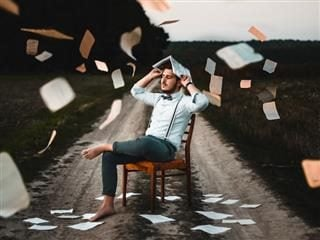 barefoot man sitting outdoors on a chair with papers flying around him. he shields his head with a book