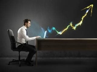 Man working hard at desk with electric charge shooting upward in the shape of a bar graph