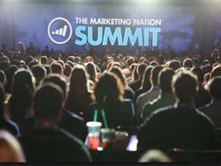 People in the crowd at the Marketing Nation Summit focus on the stage.