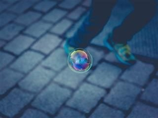 bubble on sidewalk in front of person's legs