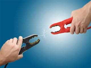 Hands holding jump start connectors with sparks flowing between