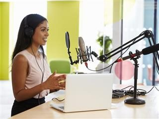 Female marketer creating a podcast in a studio