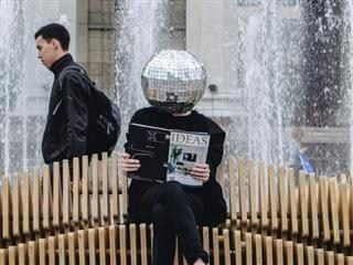person with a disco ball where their head usually is, reading a magazine