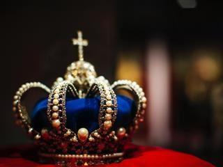 couronne bleue et or sur un coussin de velours rouge