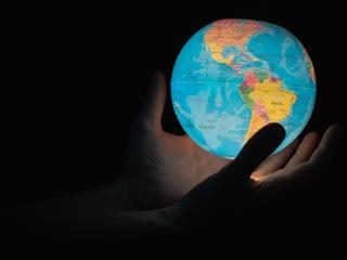 illuminated globe showing north and south america in a person's hands against a dark background