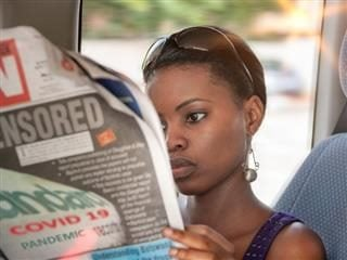 Woman sitting down reading a newspaper.