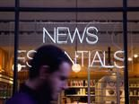 "man walking past neon sign that says ""NEWS"""