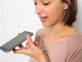 Young woman using voice search to answer a question