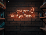 A neon sign that reads, you are what you listen to, hung on a brick wall - customer listening concept