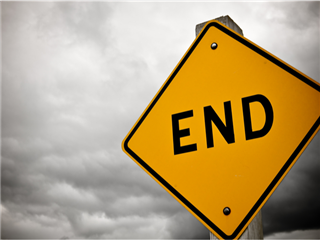 "A street sign that says ""end"" on a backdrop of a stormy sky"