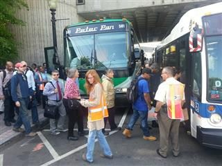 People wait in line to get on a bus.