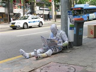 Man sitting on the ground, covered in newspapers from head to toe, reading a newspaper.