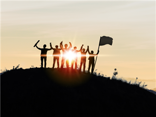 Silhouette of Business team show arm up and flag on top of the mountain.