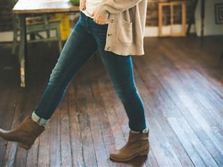 woman in brown booties taking a step on a wooden floor