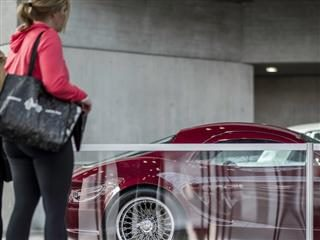 woman looking at a new car through a plastic divider