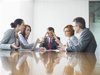 Businesspeople arguing across a conference table, a manger sits at the end with an exasperated look - conflict management concept
