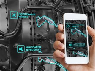 A mechanic using a smartphone augmented reality app to find areas of the engine that need maintenance