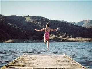 woman jumping off a dock into a lake