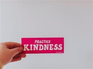 "hand holding a ""practice kindness"" bumper sticker — another version of the ""golden rule"""