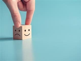 fingers on a cube with one side showing a happy face and the other side showing a sad