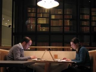 couple facing each other working on laptops