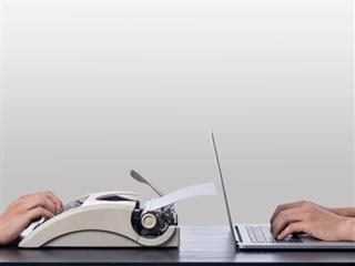 Typewriter vs laptop on a desk with a white wall background - Old vs New Concept