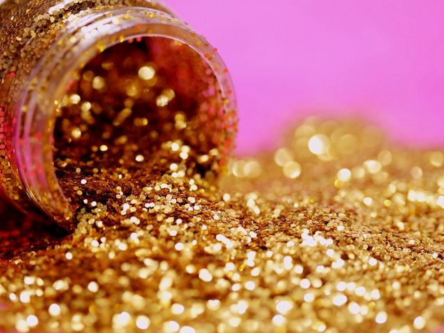 canister of gold glitter tipped on its side
