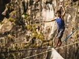 A man walking a tightrope across a canyon