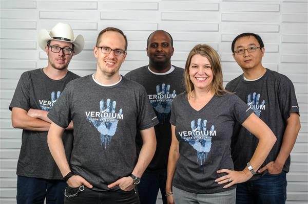 Five members of the Veridium company posing wearing company-branded T-Shirts.