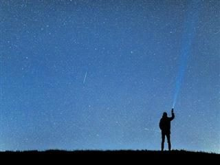person standing looking  at the night sky holding a flashlight. photo shopped beam of light against  the night sky