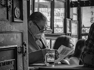 man reading the newspaper in a cafe while drinking a beer