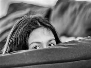 someone  hiding behind a couch