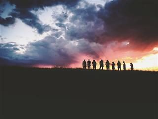group of friends silhouetted against backdrop of a sunset