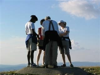 Four people gather in a huddle on top of a hill.