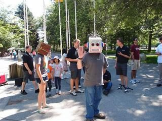 A man wearing a robot mask waving to the camera.