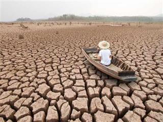 Change managed poorly: A man on wood boat in a dried up lake bed