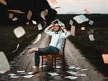 man sitting around with papers flying around him