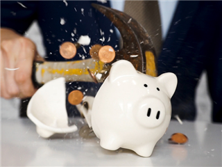 A businessman smashing a piggy bank