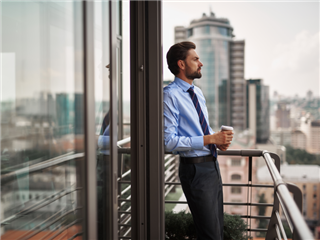 A businessman standing on office balcony with cup of coffee, looking at a clouded city view