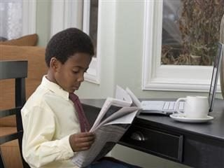 A young boy in a shirt and tie sits down and reads a newspaper.