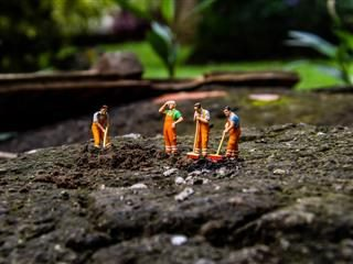 miniature figures working in a garden