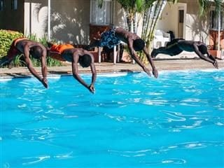 four friend diving into a pool at the same time