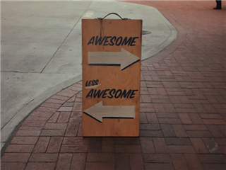 A sign on the street with two arrows pointing in different directions. One arrow says Awesome above it, the other arrow has less awesome above it. - Voice of the customer concept
