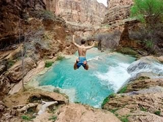 man in mid-air, jumping into a body of clear blue water